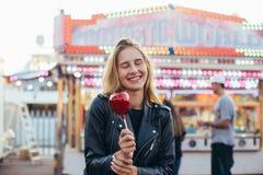 La belle femme blonde sourit avec la sucrerie de pomme images libres de droits