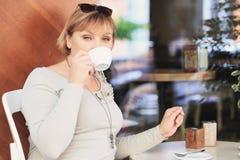 La belle femme boit du café dans le café et regarde dans l'appareil-photo Photo stock