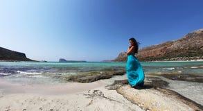 La belle femme chique sur une plage avec l'espace libre de turquoise arrose Photographie stock libre de droits