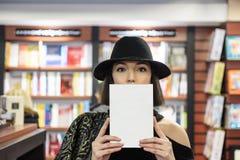 La belle femme couvre son visage de livre images stock