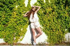 La belle femme décontractée avec de longs cheveux de châtaigne se tenant au mur a tortillé avec le lierre appréciant le soleil Photo stock