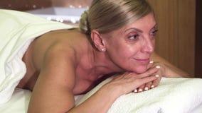 La belle femme détend le mensonge sur la table de massage photographie stock libre de droits