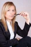 La belle femme d'affaires avec ballpen dans la bouche Image stock