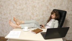 La belle femme d'affaires avec le t?l?phone s'assied dans une chaise avec les pieds nus sur le repos de table la fille au travail clips vidéos