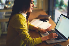 La belle femme d'affaires avec les cheveux foncés et le chandail jaune travaille dans coworking Image stock