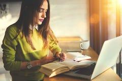 La belle femme d'affaires avec les cheveux foncés et le chandail jaune travaille dans des sources coworking et de Web recherchant Photos libres de droits
