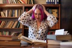 La belle femme d'affaires avec les cheveux roses lit des livres dans la bibliothèque image stock