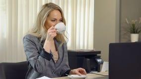 La belle femme d'affaires dans le costume travaille avec du café de tasse sur le lieu de travail photo stock