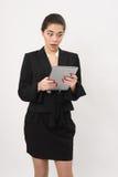 La belle femme d'affaires regarde fixement dans un comprimé Photo libre de droits