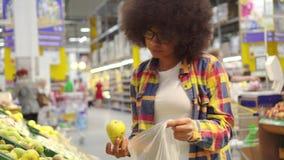 La belle femme d'afro-américain avec une coiffure Afro achète le fruit dans le supermarché banque de vidéos