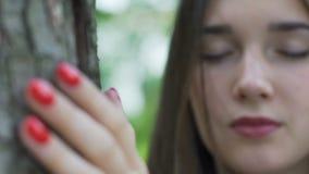 La belle femme dans l'amour avec la nature écoute un arbre, contact de main a fermé des yeux clips vidéos