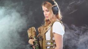 La belle femme dans l'arme militaire de participation d'équipement dans des mains se tient à l'arrière-plan fumeux Mouvement lent banque de vidéos