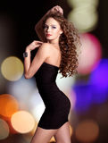 La belle femme dans la robe noire pose au-dessus des lumières de nuit Photos stock