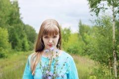 La belle femme dans le bleu tient des fleurs de chicorée Image stock