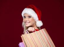 La belle femme dans le capuchon de Noël remet des paquets image stock