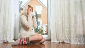 La belle femme dans le chandail s'asseyent sur le plancher près de la fenêtre parlant au téléphone, thé de boissons banque de vidéos