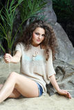 La belle femme dans le chemisier s'assied sur le sable à côté des roches grises Photos libres de droits