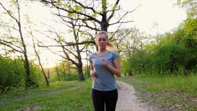 La belle femme dans le T-shirt fait pour courir au printemps la forêt banque de vidéos