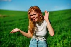 La belle femme dans la nature essaye de comprendre quelqu'un par l'essai d'entendre quelque chose avec mettre sa main à ses oreil image stock