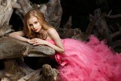 La belle femme dans la robe de soirée rose avec la jupe aérienne pelucheuse pose dans le jardin botanique sur le bois de flottage image stock