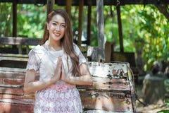 La belle femme dans la robe traditionnelle thaïlandaise est respect de salaire image stock