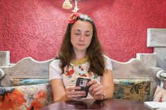 La belle femme dans un café utilise un smartphone La belle jeune femme utilise un smartphone tout en se reposant dans un café Fem images stock