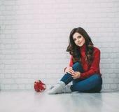 La belle femme dans un chandail rouge et un coeur forment le cadeau Images libres de droits