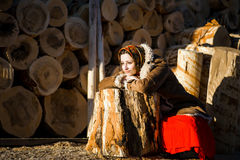La belle femme dans un manteau et une écharpe de peau de mouton s'assied se penchant sur une ouverture le fond de grands firewood Photo stock
