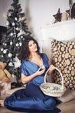 La belle femme de brune dans la robe bleue pendant la nouvelle année a décoré l'international Photographie stock