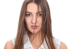 La belle femme de brune dans un chemisier blanc et un vent léger a soufflé ses cheveux Fond d'isolement Image libre de droits