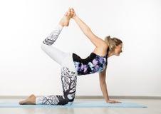 La belle femme de forme physique étirant des jambes faisant la jambe de pilates étire des exercices dans le gymnase photo libre de droits
