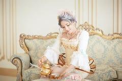 La belle femme de greyhead dans les rococos habillent la pose devant le fond rose tout en versant le thé de la bouilloire photo libre de droits