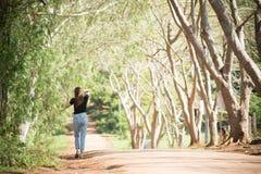 La belle femme de l'Asie dans le T-shirt noir et les jeans se tiennent sur roa image libre de droits