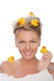 La belle femme de sourire avec des canards et le savon écument Photographie stock