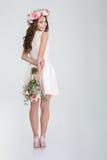La belle femme de sourire dans les roses tressent le bouquet de dissimulation des fleurs Photos libres de droits