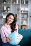 La belle femme de sourire regarde un modèle du globe se reposant sur un sofa image stock