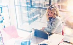 La belle femme de sourire travaillant au bureau moderne tracent Collègue à l'aide de la tablette électronique de contact sur le l images libres de droits