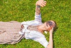 La belle femme de style de boho avec beaucoup d'accessoires se trouve sur l'herbe verte Mometn heureux photos libres de droits