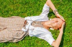 La belle femme de style de boho avec beaucoup d'accessoires se trouve sur l'herbe verte Mometn heureux image libre de droits