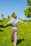 La belle femme de style de boho marche sur l'herbe et appr?cie l'heure d'?t? en parc photographie stock libre de droits