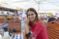 La belle femme de touristes en nourriture de attente de restaurant local s'asseyent photo libre de droits
