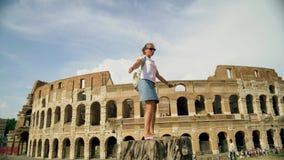 La belle femme de touristes pose pr?s du colosseum romain Mouvement lent clips vidéos