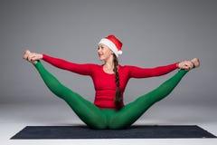 La belle femme de yoga dans le yoga de pratique en matière de chapeau de Santa pose sur le fond gris Photos libres de droits