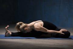 La belle femme de yoga s'asseyant dans la tête au genou plient en avant la pose Photographie stock libre de droits