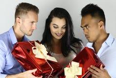 La belle femme doit choisir un des hommes concurrence des amis avec des cadeaux Photos stock