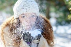 La belle femme en hiver souffle la neige avec des mains image stock