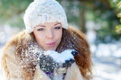 La belle femme en hiver souffle la neige avec des mains images libres de droits