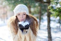 La belle femme en hiver souffle la neige avec des mains photographie stock libre de droits