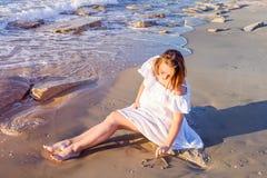 La belle femme enceinte dans des vêtements blancs dessinant un coeur forment dans le sable sur la plage près de la mer Futur conc Photographie stock libre de droits