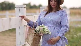 La belle femme enceinte dans la marche bleue de robe entendent la ferme Sac tricoté avec le bouquet des fleurs Fond d'arbre clips vidéos